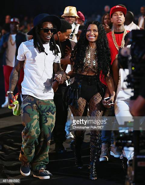 Rapper Lil Wayne singer Nicki Minaj and rapper Tyga walk onstage during the BET AWARDS '14 at Nokia Theatre LA LIVE on June 29 2014 in Los Angeles...