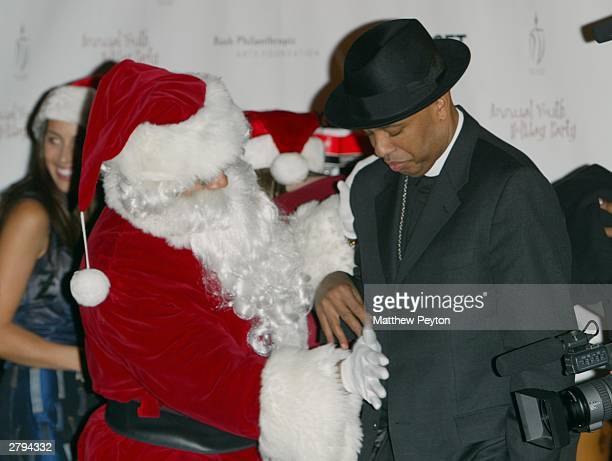 Rappers LL Cool J dressed as Santa Claus and Reverend Run help celebrate at a party for 250 disadvantaged youths December 8 2003 in New York City The...