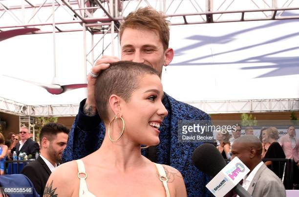 """Rapper Machine Gun Kelly jokes with singer Halsey while she is interviewed by SiriusXM on SiriusXM's """"Hits 1 in Hollywood"""" on the red carpet leading..."""