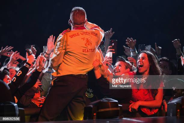 Rapper Macklemore climbs into the crowd as fans scream and grab his jacket during the 'Gemini' tour at KeyArena on December 23 2017 in Seattle...