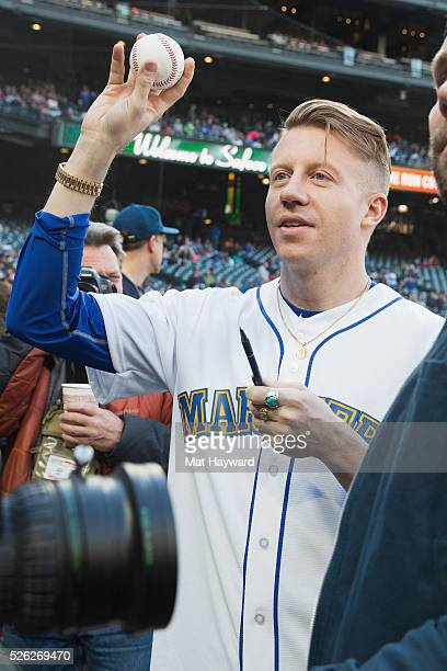 Rapper Macklemore holds a baseball before throwing out the first pitch of the Seattle Mariners vs Kansas City Royals game during ''Bumbershoot Night'...