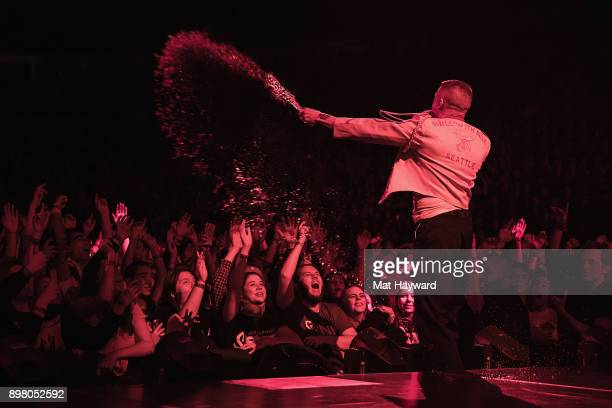 Rapper Macklemore sprays water from a bottle into the sold out crowd during his last US stop on the 'Gemini' tour at KeyArena on December 23 2017 in...
