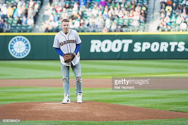 Rapper Macklemore throws the first pitch of the Seattle Mariners vs Kansas City Royals Major League Baseball game during ''Bumbershoot Night' at...