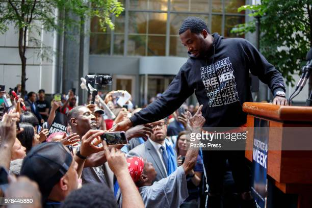 Rapper Meek Mill greets fans at a rally outside the courthouse where he returns today, continuing to seek a new trial on charges he's been fighting...