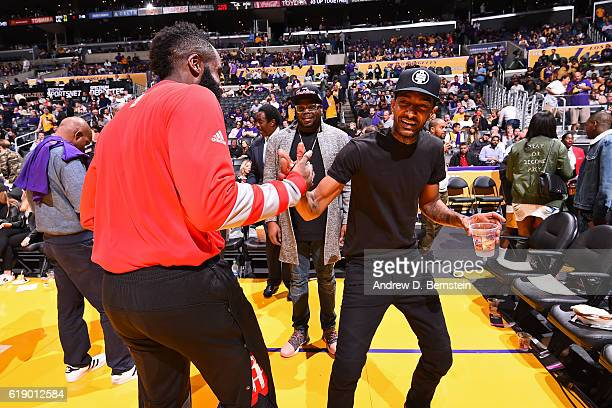 Rapper Nipsey Hussle shakes hands with James Harden of the Houston Rockets before the game against the Los Angeles Lakers on October 26 2016 at...