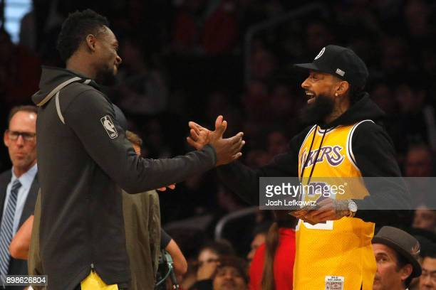 Rapper Nipsey Hussle shakes hands with Julius Randle of the Los Angeles Lakers before the game against the Minnesota Timberwolves at Staples Center...