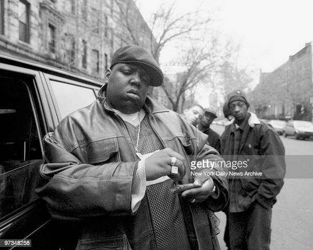 Rapper Notorious BIG aka Biggie Smalls aka Chris Wallace rolls a cigar outside his mother's house in Brooklyn