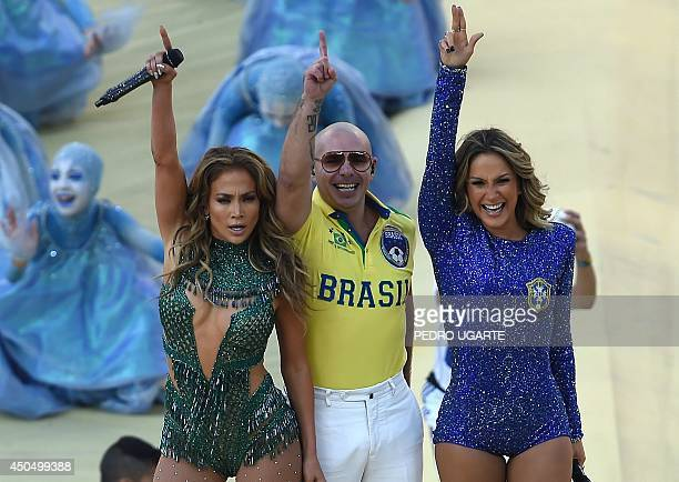 US rapper Pitbull Brazilian pop singer Claudia Leitte and US singer Jennifer Lopez salute the audience as they take part in the opening ceremony of...