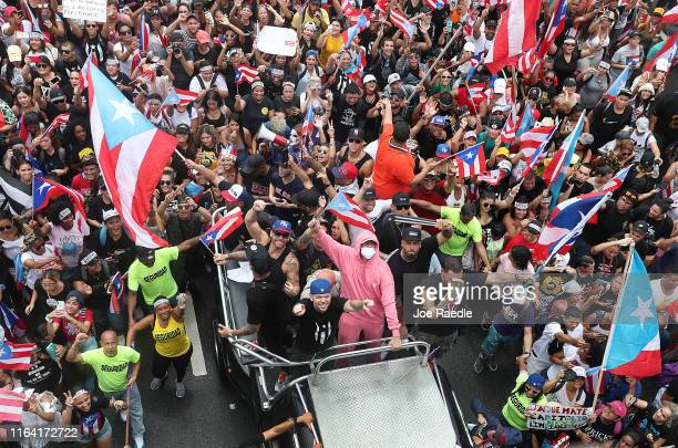 Rapper Residente and rapper Bad Bunny join with people marching through the financial district as they celebrate the ousting of Ricardo Rossello the...