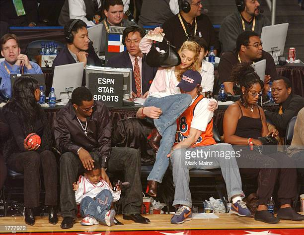 Rapper Sean P Diddy Combs watches as actor Ashton Kutcher helps actress Brittany Murphy back into her seat during the 2003 NBA AllStar game at the...