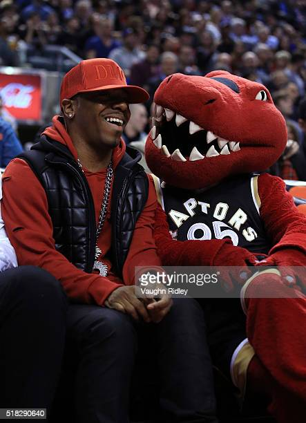 Rapper Sisqo hangs out with Toronto Raptors mascot The Raptor from his courtside seat during the first half of an NBA game between the Atlanta Hawks...