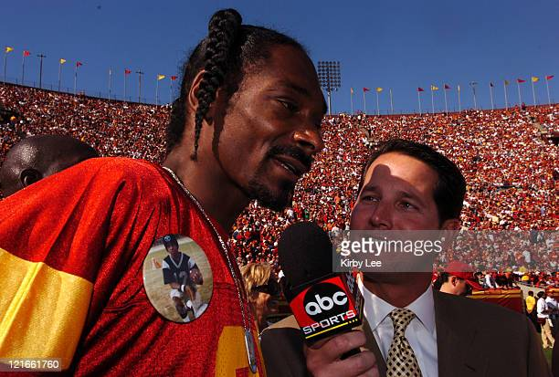 Rapper Snoop Dogg aka Calvin Broadus is interviewed by ABC Sports sideline reporter Todd Harris while wearing a No 21 LenDale White jersey during the...