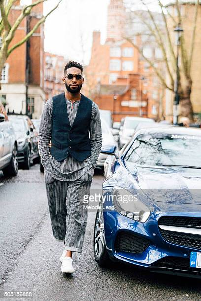Rapper Tinie Tempah arrives at the Coach show in a Mercedez Benz wearing a blue vest over a striped loose top and cuffed pants and white sneakers...