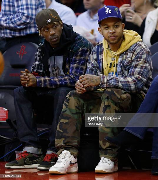 Rapper Travis Scott left watches courtside as the Golden State Warriors play the Houston Rockets at Toyota Center on March 13 2019 in Houston Texas...