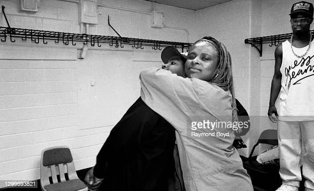 Rapper Yo-Yo playfully chokes out Ice Cube as deejay Sir Jinx looks on backstage at The Arena in St. Louis, Missouri in August 1990.