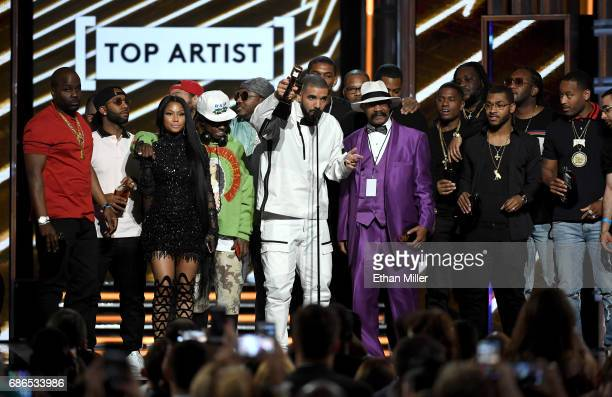 Rappers Nicki Minaj and Lil' Wayne look on as recording artist Drake accepts the Top Artist award onstage with his father Dennis Graham during the...
