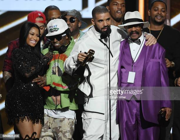Rappers Nicki Minaj and Lil' Wayne look on as recording artist Drake accepts the Top Artist award with his father Dennis Graham during the 2017...