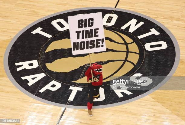 Raptor the mascot of the Toronto Raptors holds a sign at center court imploring fans to make noise over the team logo decal on Welcome Toronto night...