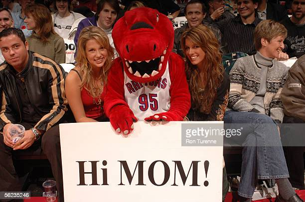 Raptor the mascot of the Toronto Raptors holds a sign that reads Hi Mom as he poses for a picture with actresses Miriam McDonald and Shenae Grimes...