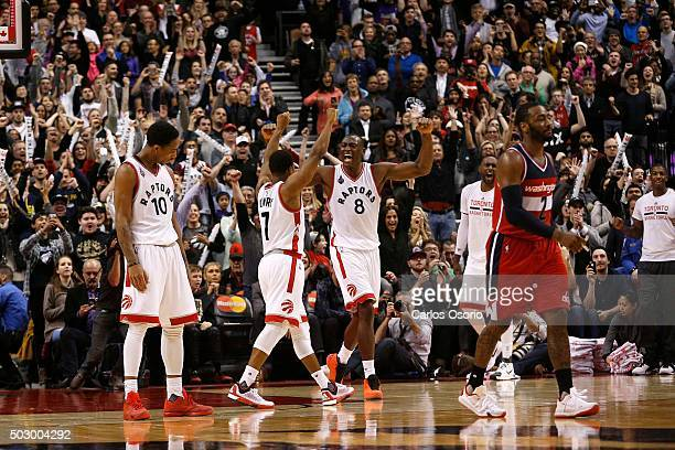 Raptors celebrate DeMar DeRozan, Kyle Lowry, Bismack Biyombo as Wizards John Wall walks off the court at the end of the NBA game between the Toronto...