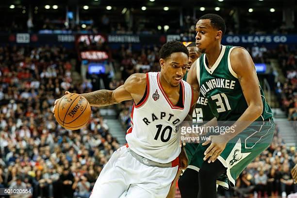 Raptors' guard DeMar DeRozan gets around Bucks' forward John Henson in 2nd half action in Toronto Raptors vs Milwaukee Bucks in NBA regular season...