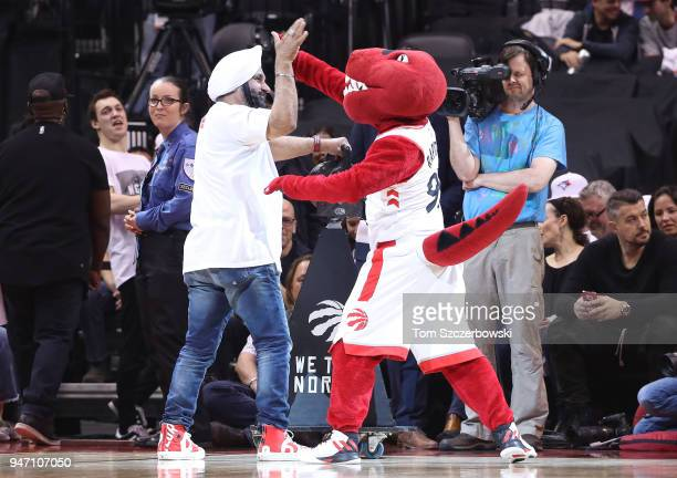Raptors Superfan Nav Bhatia high-fives Raptor the mascot of the Toronto Raptors during a break in the action of the game against the Washington...