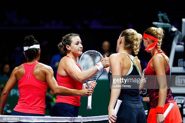 Raquel KopsJones and Abigail Spears of the USA congratulate Timea Babos of Hungary and Kristina Mladenovic of France for defeating them in a doubles...