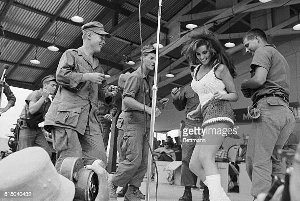 Raquel Welch dances on stage with a group of soldiers during a Bob Hope USO show at Da Nang Vietnam