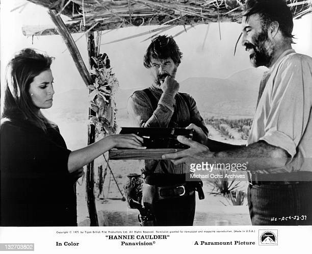 Raquel Welch grabbing item from box while Robert Culp watches in a scene from the film 'Hannie Caulder' 1971