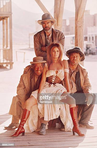 Raquel Welch sits on the lap of actor Ernest Borgnine in this publicity still for the movie Hannie Caulder 1971 Jack Elam stands behind them while to...
