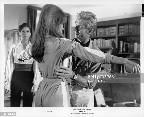 Raquel Welch stands with arms wide while Anthony Franciosa holds her at her waist in a scene from the film 'Fathom' 1967