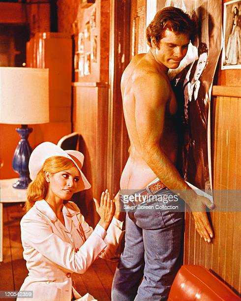 Raquel Welch US actress wearing a white widebrimmed hat as she sits behind Roger Herren US actor who has his jeans down exposing his buttocks as he...
