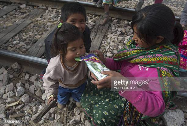 Raramuris indigenous girl gives milk to her sister after recives humanitarian aid carried by Mexican Red Cross at the train station in Pitoreal town,...