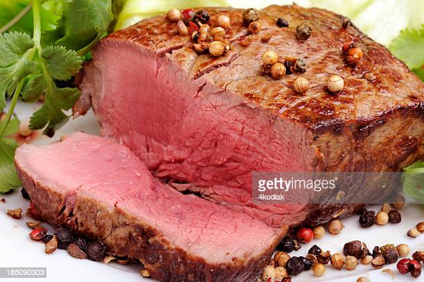 Rare steak with green salad on a white background
