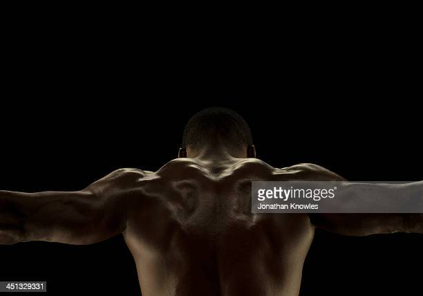 Rare view of athletic male, arms outstretched