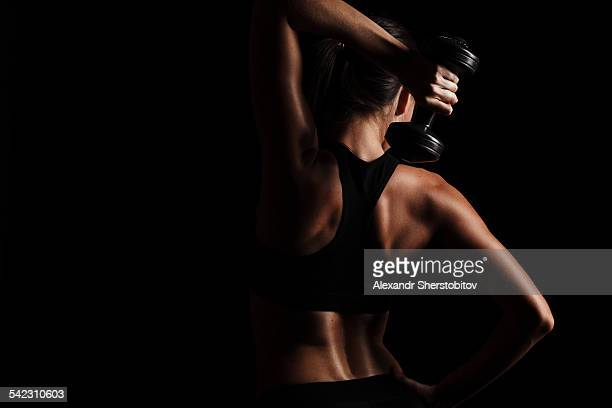 Rare view of female body, exercising with dumbbell