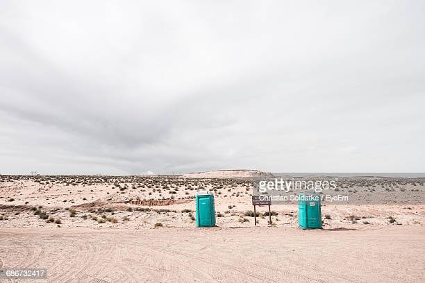 Rare View Of Portable Toilets In Front Of A Dune On Beach Against Sky