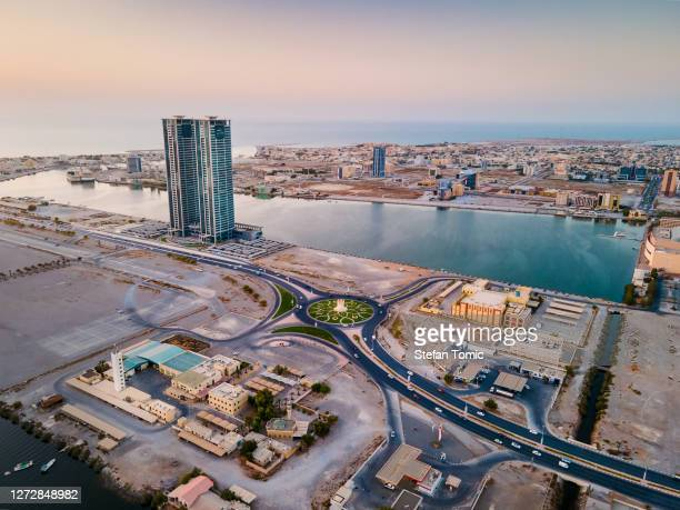 ras al khaimah emirate cityscape skyline rising over the mangroves and the creek in the united arab emirates at sunset - ras al khaimah stock pictures, royalty-free photos & images