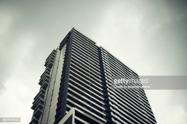 Rascacielos. Edificio muy alto de cristal y metálico donde se refleja la luz del día sobre un cielo gris con algunas nubes. Escena tomada desde abajo.