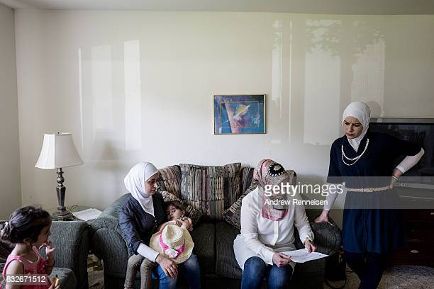 Rasha Basha a Syrian community volunteer left helps the Al Hayek family with medical paperwork at their home on July 23 2015 in Bloomfield Hills...
