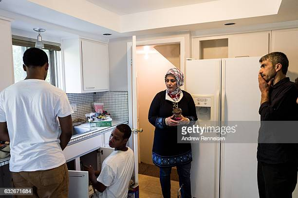Rasha Basha a Syrian community volunteer talks to workers finishing the Tanbal Family home on July 24 2015 in Bloomfield Hills Michigan Since the war...