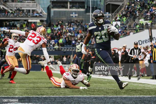 Rashaad Penny of the Seattle Seahawks avoids a tackle by Antone Exum of the San Francisco 49ers for a touchdown in the third quarter at CenturyLink...