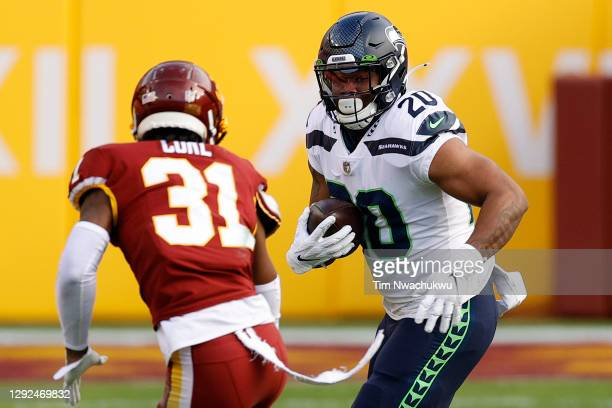 Rashaad Penny of the Seattle Seahawks breaks a tackle attempt by Kamren Curl of the Washington Football Team at FedExField on December 20, 2020 in...