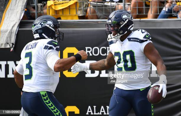 Rashaad Penny of the Seattle Seahawks celebrates his touchdown with Russell Wilson during the third quarter against the Pittsburgh Steelers at Heinz...