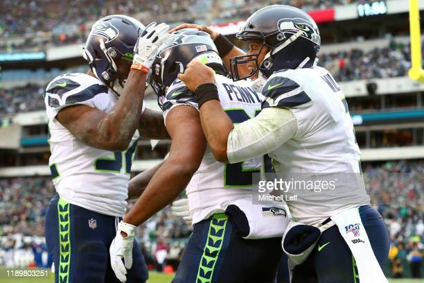 Rashaad Penny of the Seattle Seahawks celebrates with Russell Wilson and Chris Carson after rushing for a fourth quarter touchdown against the...