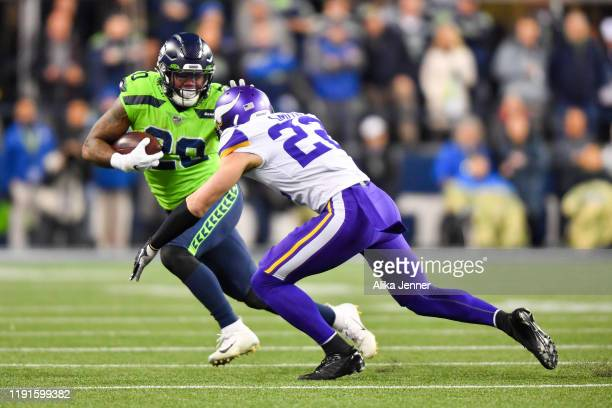 Rashaad Penny of the Seattle Seahawks gives Harrison Smith of the Minnesota Vikings a stiff arm during the game at CenturyLink Field on December 02,...