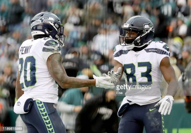 Rashaad Penny of the Seattle Seahawks is congratulated by teammate David Moore after he scored in the fourth quarter against the Philadelphia Eagles...