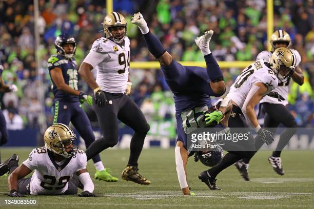 Rashaad Penny of the Seattle Seahawks is tripped up by Paulson Adebo of the New Orleans Saints during the first half at Lumen Field on October 25,...