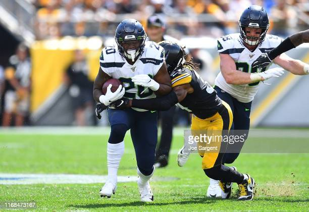 Rashaad Penny of the Seattle Seahawks is wrapped up by Terrell Edmunds of the Pittsburgh Steelers during the second quarter at Heinz Field on...