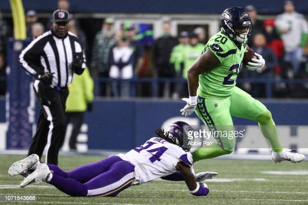 Rashaad Penny of the Seattle Seahawks looks to avoid a tackle by Holton Hill of the Minnesota Vikings in the second quarter at CenturyLink Field on...